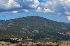 Himla- landskap med fluffiga moln ovanför berget royaltyfri fotografi