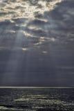 Himla- strålar över havet Arkivfoto