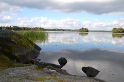Himlar reflekterade i sjön Arkivfoto