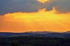Himlen på solnedgången över skogar och forested berg Arkivbild