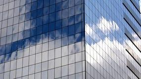 Himlen reflekterade i Windows av en skyskrapa Arkivfoton