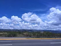Himmel, Berge, Wiesen und Straße Stockbilder