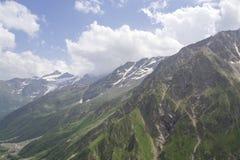Himmel i molnen gör grön och snöar på bergen, den norr Kaukasus Elbrus regionen Arkivbild