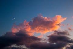 Himmel med månen och steg moln under solnedgång Arkivbilder