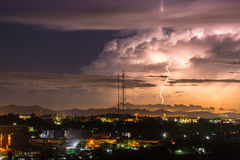 Himmel mit auffallenden Hügeln des Blitzes hinter Kleinstadt lizenzfreie stockbilder