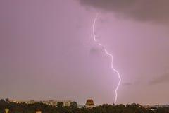 Himmel mit auffallenden Hügeln des Blitzes hinter Kleinstadt stockbild