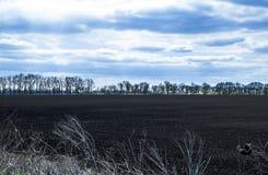 Himmel mit Wolken über schwarzen Feldern Stockbilder