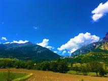 Himmel, moln, berg och fält arkivfoto