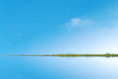 Himmel och vatten som delas av gräs- Landstrip Arkivbild