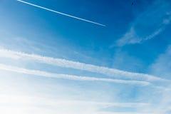 Himmel täckte med Chemtrails och nivån som lämnar en Contrail, Chemtrail royaltyfri fotografi
