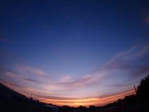 Himmel und Wolken über der Stadt nach Sonnenuntergang Lizenzfreies Stockfoto
