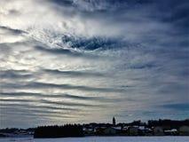 Himmel, Wolkenschnee und Stadt Stockbild