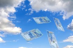 Himmelcollage Hägring - mot den blåa himlen som flyger genomskinliga ryska rubel Ny sedel 2000 rubel arkivbild