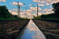 Himmelreflexion på järnvägspår arkivbilder