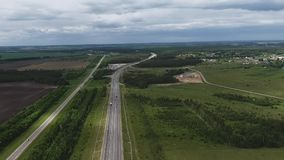 Himmelsikt av den långa breda vägen med ridningbilar, gröna fält av landsbygd arkivfilmer