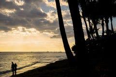 Himmelwasser und Strand silhouettierte Paare Lizenzfreie Stockfotografie
