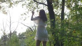 Himmlisches Weiß kleidete die Frau, die das Sonnenyoga begrüßt, das in der Natur sich entspannt - stock footage