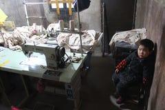 HINA - 15 JANUARI: Een kleine jongen in Chinese klerenfabriek Royalty-vrije Stock Fotografie