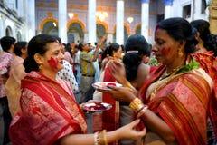 Hindische Frauen, die Gesichter mit rotem Pulver malen lizenzfreies stockfoto