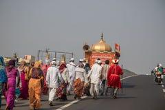 Hindische lokale Dorfmänner und -frauen gekleidet im traditionellen Kostüm, das eine religiöse Prozession entlang einer Landstraß stockfoto
