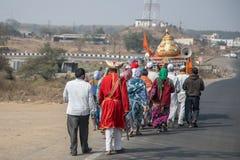 Hindische lokale Dorfmänner und -frauen gekleidet im traditionellen Kostüm, das eine religiöse Prozession entlang einer Landstraß lizenzfreie stockfotografie
