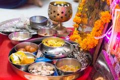 Hindische Zeremonie mit Bonbons, Münzen, Gott, Silber Wortshipping Stockfotografie