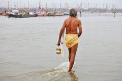Hindischer eifriger Anhänger kommt zum Zusammenströmen vom Ganges und von Yamuna-Fluss für das Ritualbaden Stockfoto