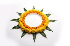 Hindisches Festivaldekoration Blume rangoli unter Verwendung der Ringelblume und Mango treiben Blätter stockfotos