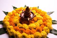 Hindisches Festivaldekoration Blume rangoli unter Verwendung der Ringelblume und Mango treiben Blätter stockbilder