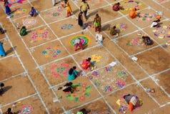 Hindisches rangoli des Frauenabgehobenen betrages mit farbigen Pulvern, Blumen im pongal oder makara sankranti festiva stockfotos
