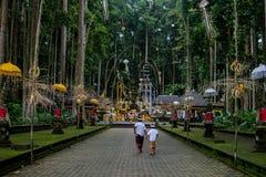 Hinditempla in Bali Familie die naar ceremonie in bos gaan royalty-vrije stock fotografie