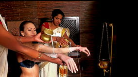 Hindu beautician pouring milk on the white woman stock footage
