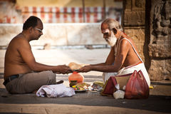 Hindu Brahmin with religious attributes blessing people at Meenakshi Temple.  India, Madurai, Tamil Nadu. MADURAI, INDIA - FEBR 16: Hindu Brahmin with religious Royalty Free Stock Image