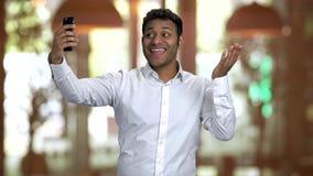 Hindu businessman posing and taking selfie using his frontal camera.