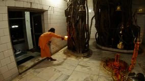 Hindu ceremony by monk Shiv a temple inside atributes decorated by flowers big banyan trees light