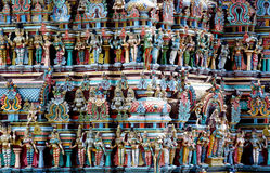 Hindu colorful Gods statues on a gopuram in India. Colored statue on the wall in front of the entrance to the hindu temple with ornament and decorations. Man and stock photography
