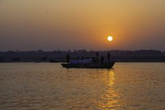 Hindu Devotees on the River Ganga. A boat full of Hindus watch and pray as the sun rises over the Ganga. The people wearing white may have cremated their family Royalty Free Stock Photography