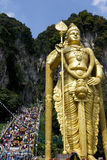 Hindu Devotees at Thaipusam Celebration. Hindu devotees and visitors at Malaysia's Thaipusam celebration. Also seen is a giant statue of Lord Murugan. This royalty free stock photo