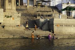 Daily Rituals Found on the Ghats. A Hindu family wash away their sins in the river Ganges whilst others offer prayers to their Gods from the Ghats of Varanasi Stock Images