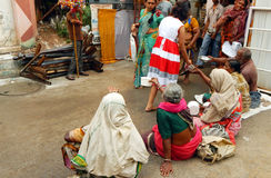 Hindu girl geeta,12,abids giving money to women begging in front of temple Stock Image