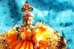 Hindu God Lord Krishna. Brass idol of baby lord Krishna, a Hindu god, dressed in bright yellow clothing, against a polka dotted aqua colored cloth background Royalty Free Stock Photos