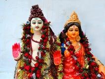 Hindu gods - Shiva and Parvati statue. Statue of Hindu gods - Shiva and Parvati against a blue wall royalty free stock photo