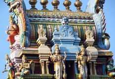Hindu gods statues on a temple gopuram. Colored statue on the wall in front of the entrance to the hindu temple with ornament and decorations. Man and woman royalty free stock images