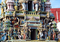 Hindu gods statues on a temple gopuram. Colored statue on the wall in front of the entrance to the hindu temple with ornament and decorations. Man and woman royalty free stock photography