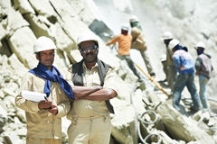 Hindu indian builders workers at construction site. Two professional indian asian engineer builders foremans with plan at mountains construction site Royalty Free Stock Image