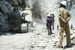 Hindu indian builders workers at construction site. Indian asian site manager engineer builder inspecting road  clearing at mountains construction site Royalty Free Stock Photos