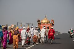 Hindu local village men and women dressed in traditional costume performing a religious procession along a highway near their vill stock photo