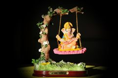 `Hinduism` Hindu God-Ganesha in art form sitting on a swing. Hindu Lord Ganesha, a symbol of success, trouble remover and prosperity. Text translation = Jai Royalty Free Stock Image