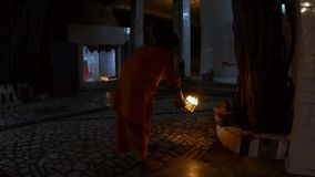 Hindu monk performs evening aarti with light fixture near banyan tree