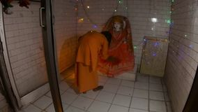 Hindu monk performs night religious ritual aarti with fan light near statue of Goddess flashlights